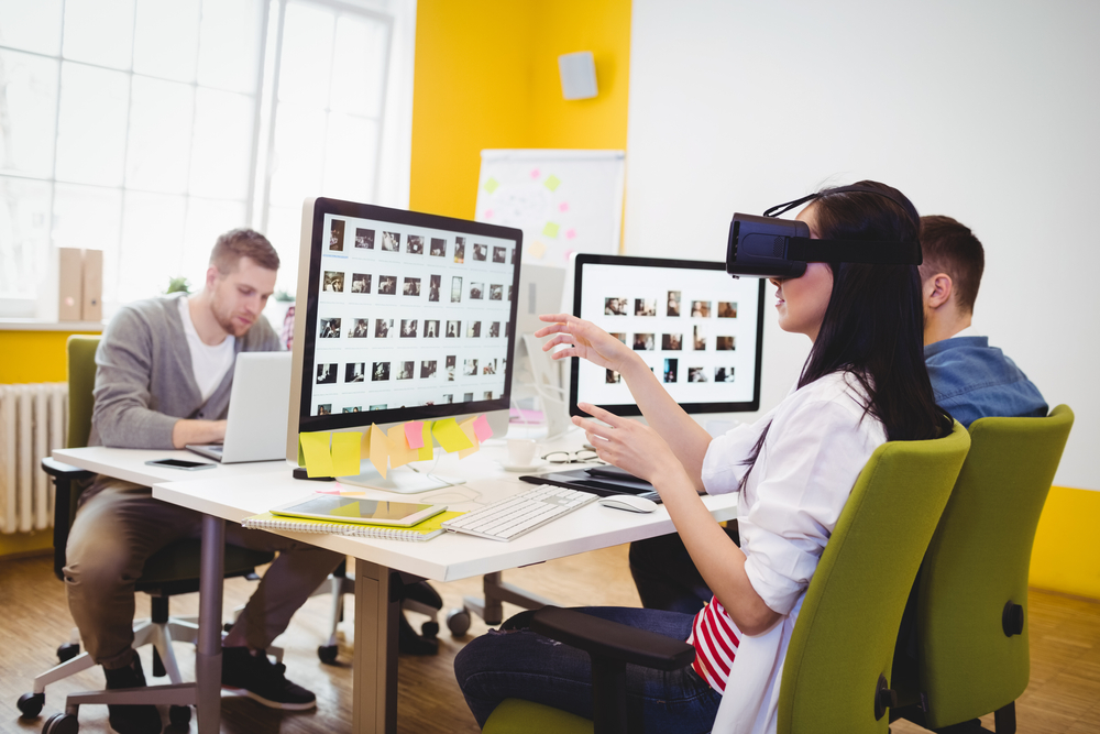 Yoiung female executive enjoying augmented reality headset with colleagues sitting at creative office-1